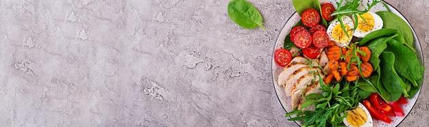 Plaat met een keto dieetvoeding. cherrytomaatjes, kipfilet, eieren, wortel, salade met rucola en spinazie. keto lunch. bovenaanzicht Gratis Foto