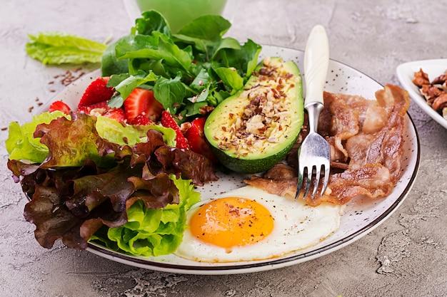 Plaat met een keto dieetvoeding. gebakken ei, spek, avocado, rucola en aardbeien. keto ontbijt. Gratis Foto
