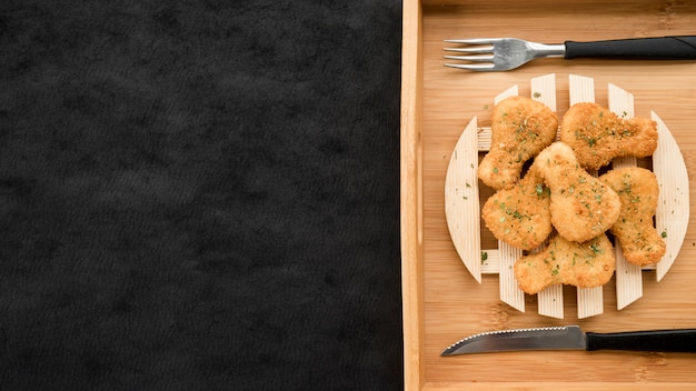 Plaat met kippengoudklompjes op houten dienblad Gratis Foto