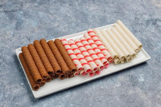 Plaat met smakelijke wafer roll sticks op betonnen ondergrond Gratis Foto