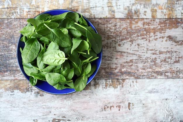 Plaat met spinazie op een houten oppervlak. Premium Foto