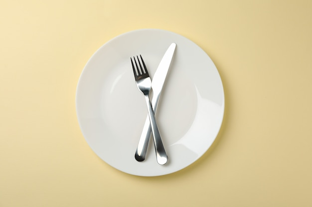 Plaat met vork en mes op beige achtergrond, bovenaanzicht Premium Foto