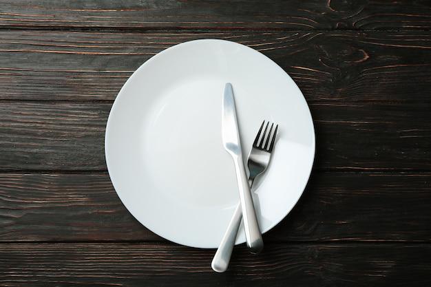 Plaat met vork en mes op houten achtergrond, bovenaanzicht Premium Foto