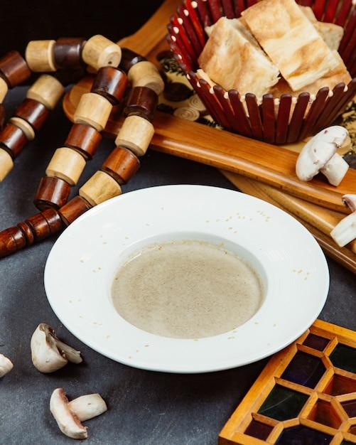 Plaat van champignonsoep geserveerd met brood Gratis Foto