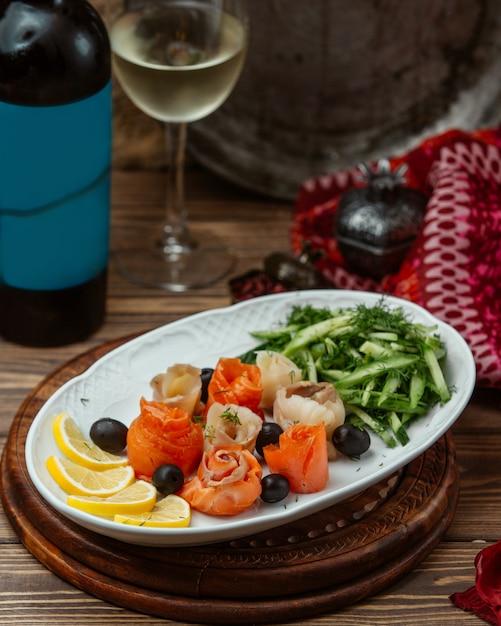 Plaat van plakjes zalm en tonijn gerold in bloemvorm met citroen Gratis Foto
