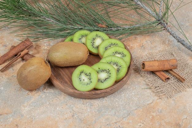 Plaat van verse kiwi en pijpjes kaneel op marmeren achtergrond. hoge kwaliteit foto Gratis Foto