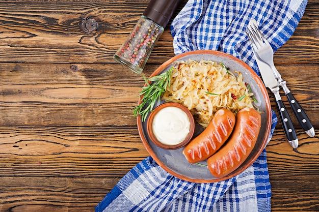 Plaat van worsten en zuurkool op houten lijst. traditioneel oktoberfest-menu. plat leggen. bovenaanzicht Gratis Foto