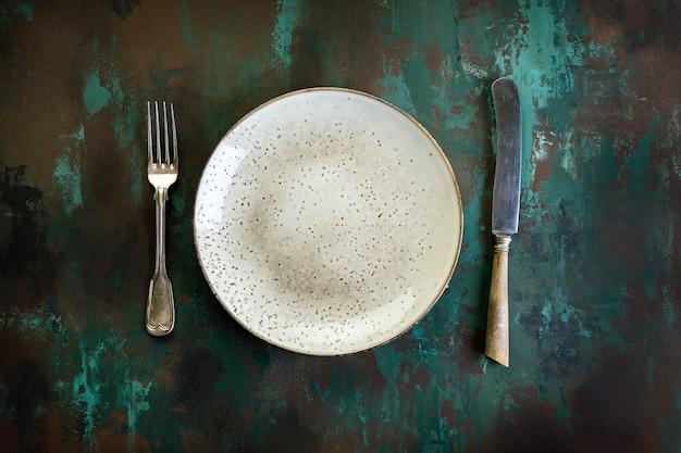 Plaat, vork en mes op een roestige metalen tafel Premium Foto