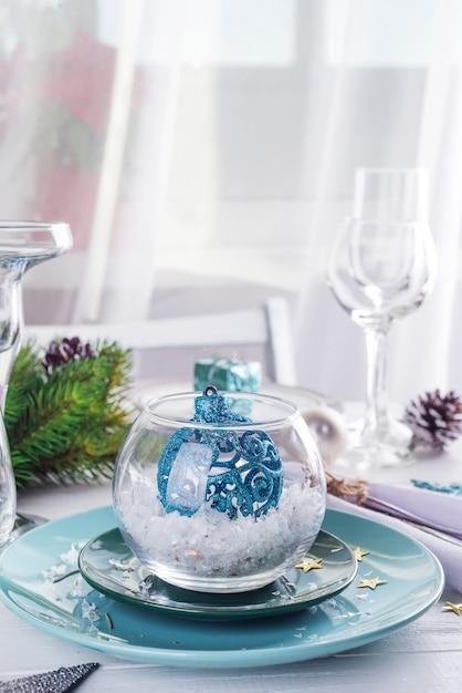 Plaats de tafel instelling voor kerstmis witte tafel met blauwe decor elementen met groene takken kerstboom Premium Foto