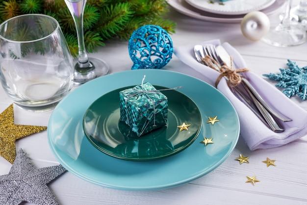 Plaats de tafel instelling voor kerstmis witte tafel met paarse decor elementen met groene takken kerstboom Premium Foto