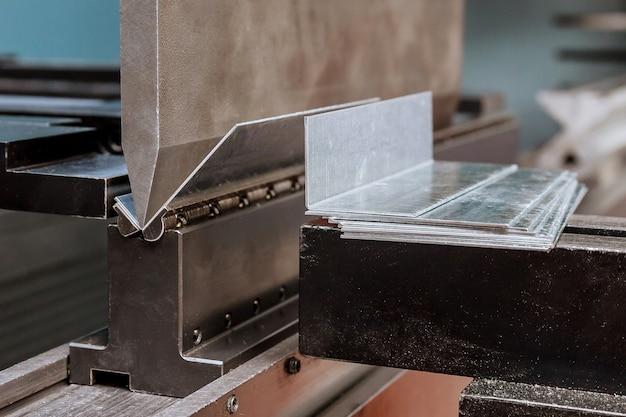 Plaatwerk buigen op een hydraulische machine in de fabriek. detailopname. Premium Foto