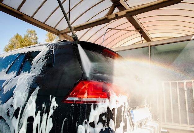 Plak spuitwater op een auto bedekt met schuim Gratis Foto