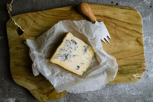 Plakje blauwe kaas op een houten bord met kaasmes Premium Foto