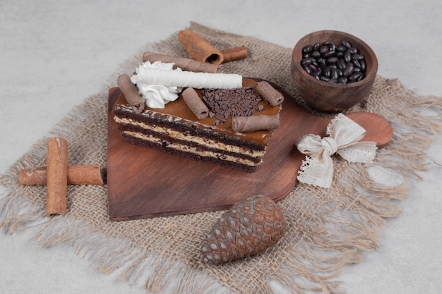 Plakje chocoladetaart, kaneel en dennenappel op jute. hoge kwaliteit foto Gratis Foto