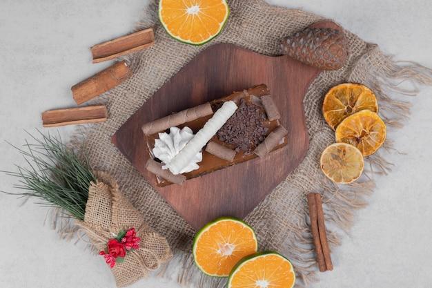 Plakje chocoladetaart, kaneel en plakjes mandarijn op jute. hoge kwaliteit foto Gratis Foto