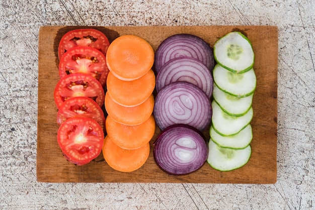 Plakje tomaten; wortels; ui en komkommer gerangschikt op houten plank over de concrete achtergrond Gratis Foto