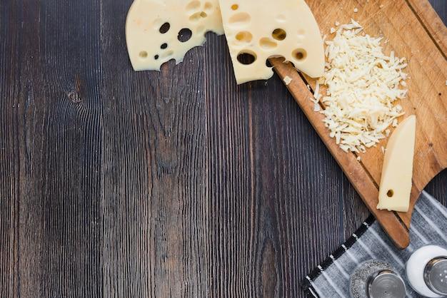 Plakjes en geraspte maasdam-kaas op een houten bord boven het zwarte bureau Gratis Foto