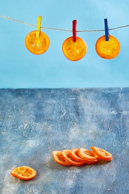Plakjes gedroogde sinaasappels of mandarijnen worden aan de waslijn gehangen met wasknijpers op een blauwe muur. vegetarisme en gezond eten. kopieer ruimte Premium Foto
