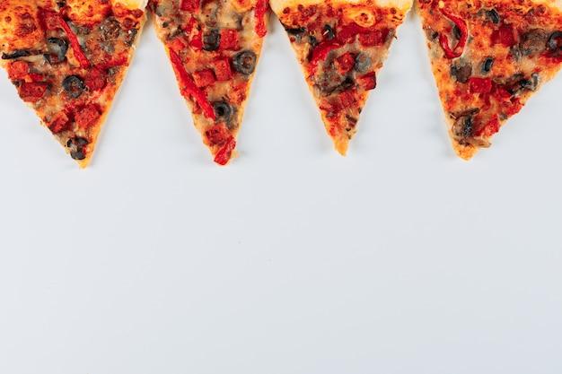 Plakjes van een pizza plat lag op een heldere stucwerk achtergrond Gratis Foto