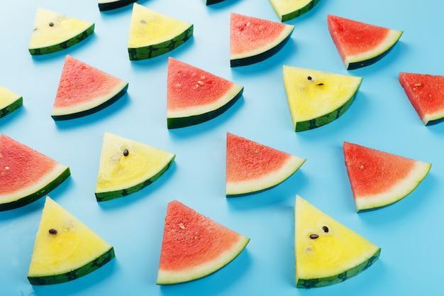 Plakjes verse plakjes gele en rode watermeloen op blauw. Premium Foto