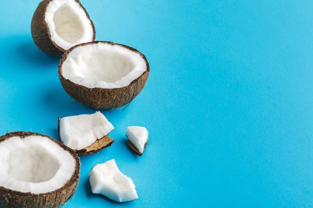 Plakken van gebroken tropische kokosnoten op blauw. bovenaanzicht Premium Foto