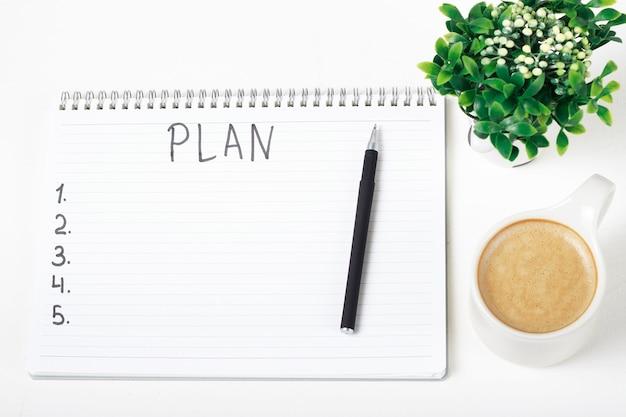 Plan op notebook, plant en kopje koffie Premium Foto