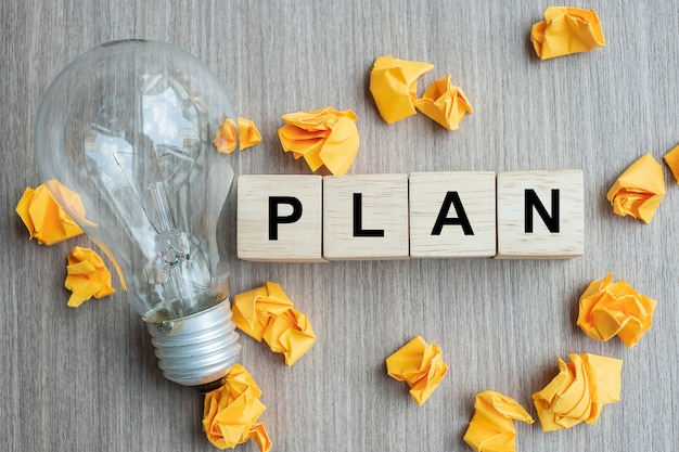Plan-tekst houten kubus en verkruimeld papier met gloeilamp Premium Foto