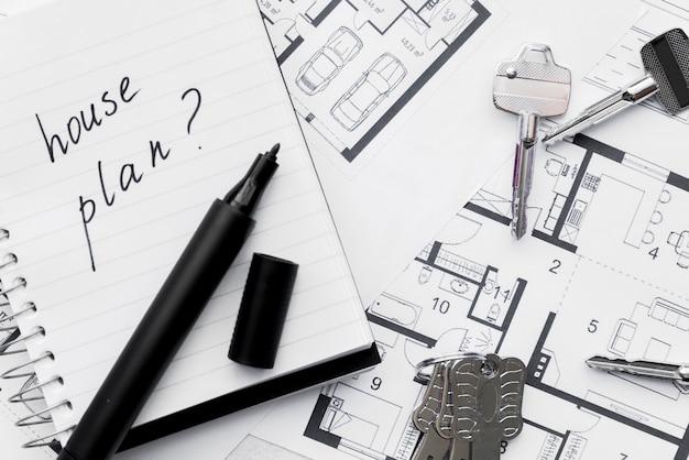 Plan van het huis met vraagteken teken geschreven op notebook met viltstift en toetsen op de blauwe print Gratis Foto