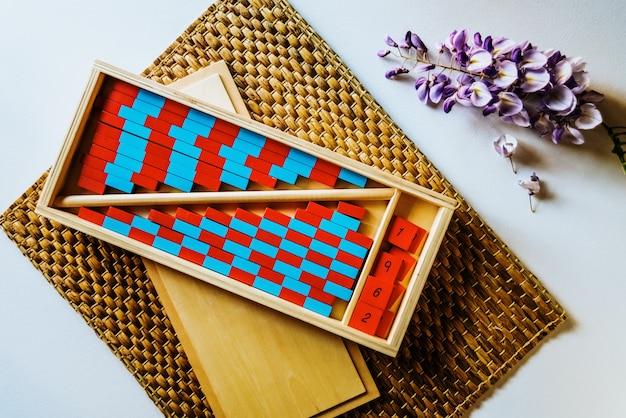 Planken van rode en blauwe houten montessori om het kind met visuele duidelijkheid, berekeningshandelingen te vergemakkelijken. Premium Foto