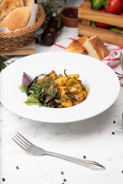 Plantaardige hutspot met vlees, maisstukjes, chili peper en groenten, basilic, peterselie in witte plaat. Gratis Foto