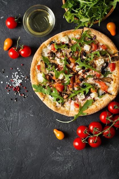 Plantaardige italiaanse pizza met tomaten op zwarte achtergrond, kopie ruimte, bovenaanzicht, verticaal Premium Foto