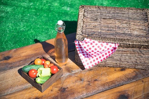 Plantaardige krat; olijfolie fles en picknickmand op houten tafel Gratis Foto