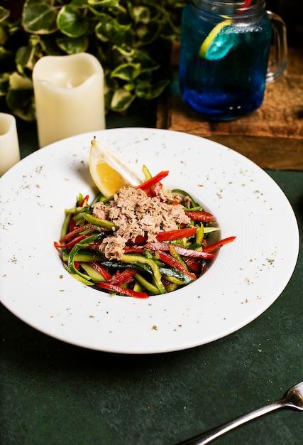 Plantaardige salade met komkommer, paprika, gehakte kip en citroen in olijfolie. Gratis Foto