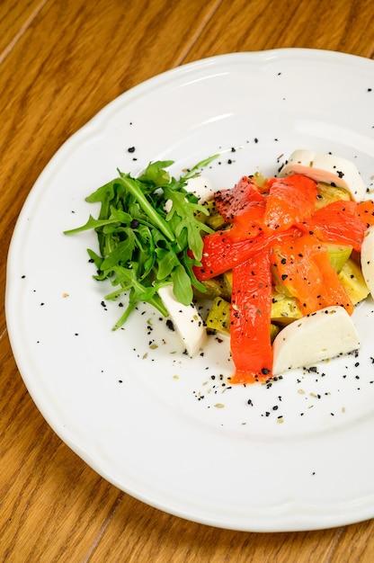 Plantaardige vegetarische salade met tomaten, paprika en uien op houten tafel. gezonde salade met verse rijpe zomergroenten Premium Foto