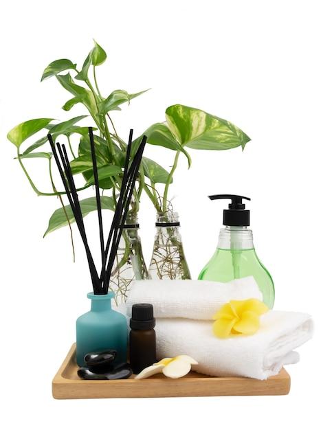 Plantkunde groen gevlekte betelvaas, wierookstokjes, plumaria-bloem, witte handdoeken`` kaars en aroma-olie in spa of badkamer geïsoleerd op een witte achtergrond, aromatherapie spa wellness Premium Foto