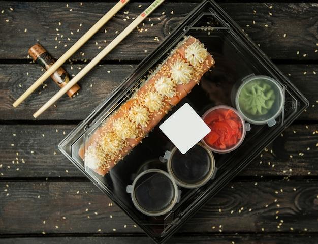 Plastic doos shushibroodjes voor levering met zalm, sauzen, wasabi, gember Gratis Foto