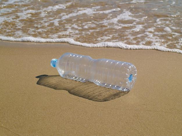 Plastic fles op het zand op het strand, verminderen, hergebruiken en recyclen plastic Premium Foto