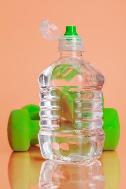 Plastic flessen water op een pastel beige achtergrond Premium Foto