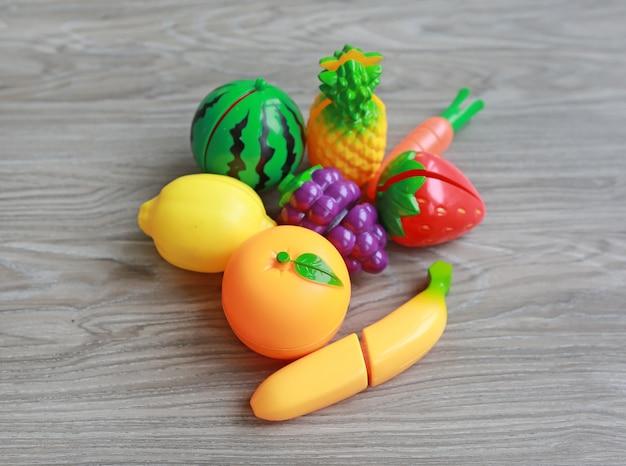 Plastic fruit op houten achtergrond, het stuk speelgoed van de kinderen Premium Foto