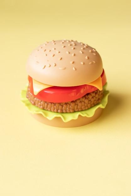 Plastic hamburger, salade, tomaat, op een gele backgroun Premium Foto