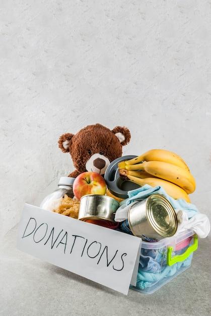 Plastic schenkingsdoos met speelgoed, kleding en voedsel op witte grijze achtergrond Premium Foto