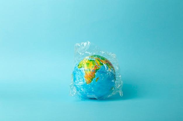 Plastic zak vervuiling concept. earth globe in een plastic zak op een gekleurde achtergrond. plastic en afvalvervuiling oceanen, natuur Premium Foto
