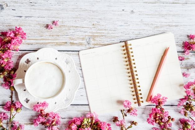 Plat bureaublad items: koffiemok, pen, notitieboekje en roze bloemen op witte houten tafel Premium Foto