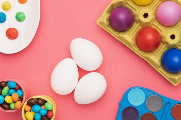 Plat gekleurde eieren en kleurgereedschap leggen Gratis Foto