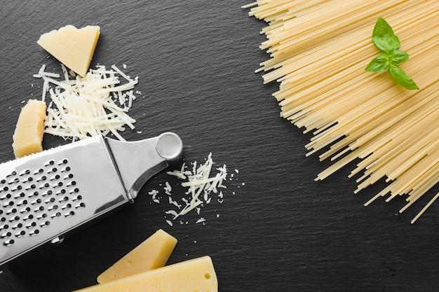 Plat geraspte parmezaanse kaas en rasp met ongekookte spaghetti Gratis Foto