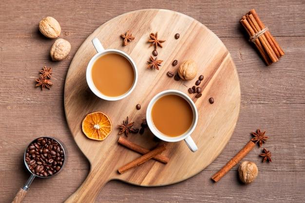 Plat koffie kopjes op een houten bord met ingrediënten Gratis Foto