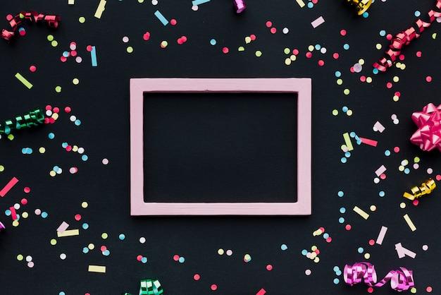 Plat lag arrangement met confetti en frame Gratis Foto