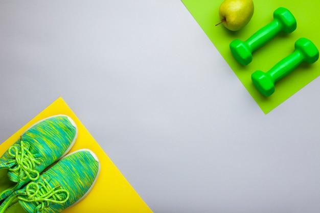 Plat lag arrangement met groene schoenen en halters Gratis Foto