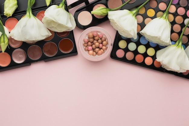 Plat lag assortiment met make-up paletten en bloemen Gratis Foto