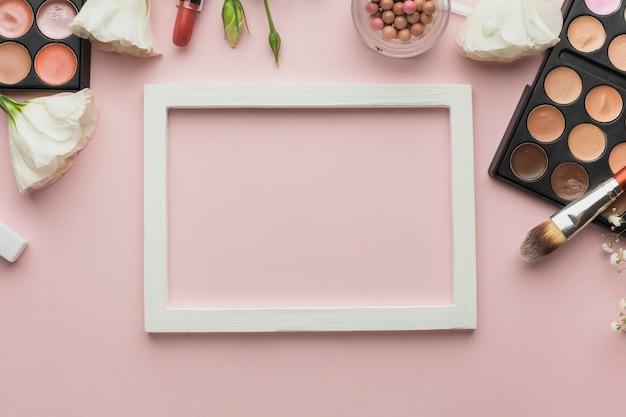 Plat lag assortiment met make-up producten en frame Gratis Foto